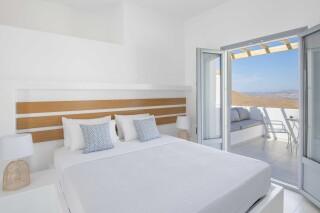 deluxe room oneiro suites bedroom with sea view